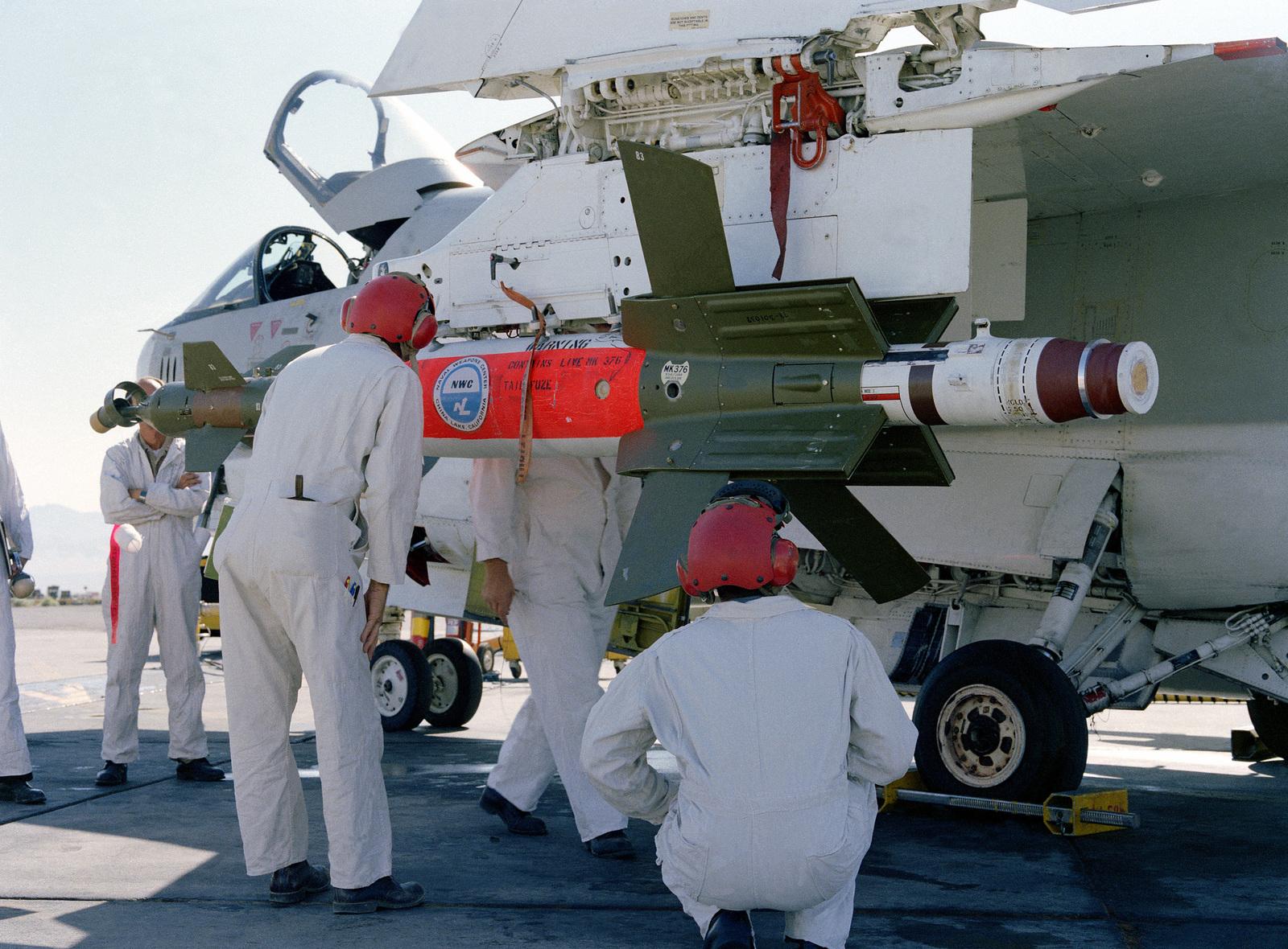 An A-7 Corsair II aircraft crew mounts a Skipper II laser guided bomb on the plane
