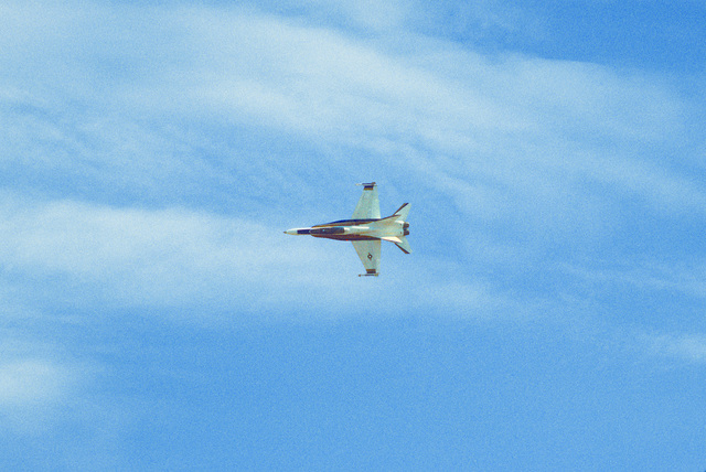 An underside view of an F-18 Hornet aircraft demonstrating flight characteristics during the air show