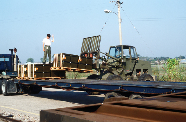 Cargo is unloaded from an Army trailer for reloading onto a flatbed railroad car with the use of a forklift. It contains a munitions shipment that arrived at the Chinhae Water Port