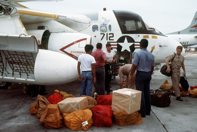 Flight and ground crewmen unload cargo from an S-3A Viking aircraft that has just landed