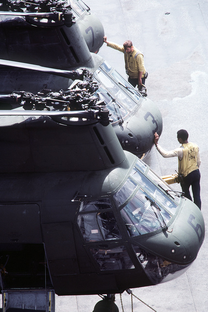 Flight deck crewmen aboard the amphibious assault ship USS SAIPAN (LHA-2) stand in front of a row of parked CH-46 Sea Knight helicopters. The SAIPAN is taking part in exercise Ocean Venture '81