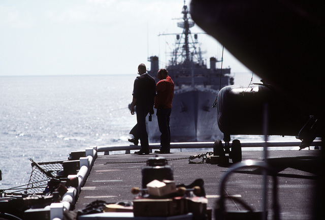 Flight deck crewmen aboard the amphibious assault ship USS SAIPAN (LPH-2) take a break as they watch U.S. and Spanish ships perform maneuvering exercises. The ships are taking part in exercise Ocean Venture '81
