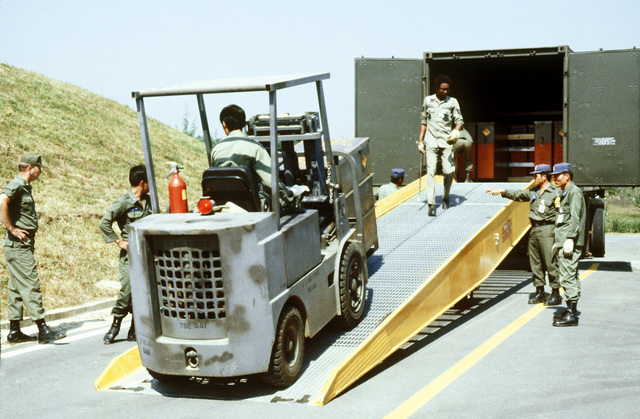 Personnel from the 51st Munitions Maintenance Squadron offload munitions from a military van with the use of a forklift