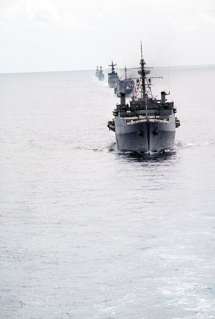 U.S. and Spanish ships cruise in formation during exercise Ocean Venture '81. The ships are led by the amphibious transport dock USS RALEIGH (LPD-1) and the tank landig ship USS BARNSTABLE COUNTRY (LST-1197)