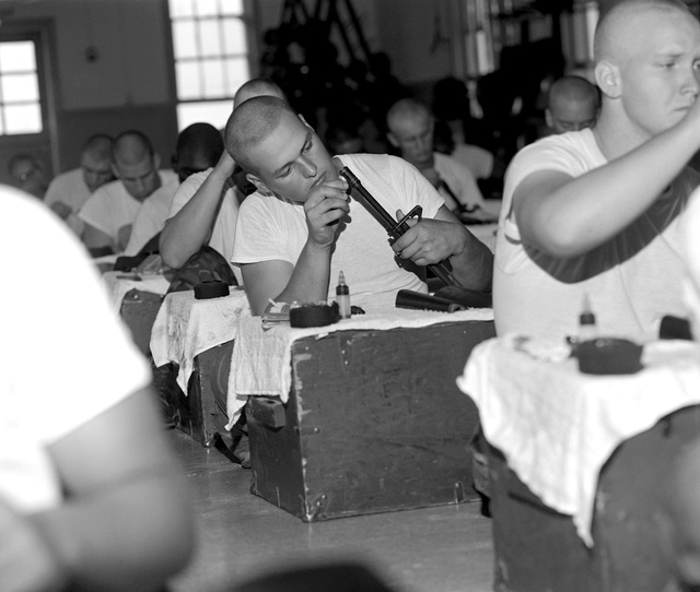 Recruits of the physical conditioning platoon clean their M-16A1 rifles in the barracks