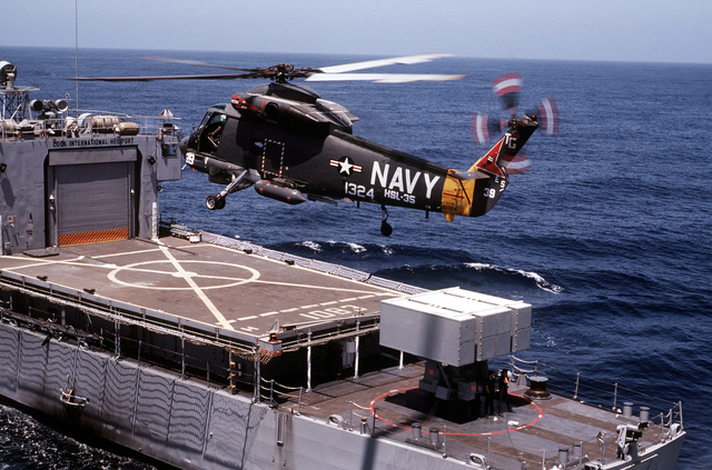 A left rear view of an SH-2F Seasprite helicopter from Light Helicopter Anti-submarine Squadron 35 (HSL-35), assigned to Anti-submarine Warfare Wing Pacific, preparing to land on the helicopter pad aboard the frigate USS COOK (FF-1083)