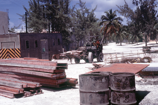 A Seabees drives a debris-carrying forklift during construction activities