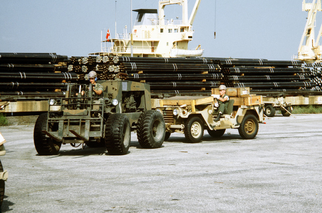 A Marine driving a forklift tows an M-151A1 jeep from a railroad flatcar to a staging area where equipment will then be loaded aboard a cargo ship in support of a possible rapid deployment of a 12,000-troop Marine amphibious brigade operation