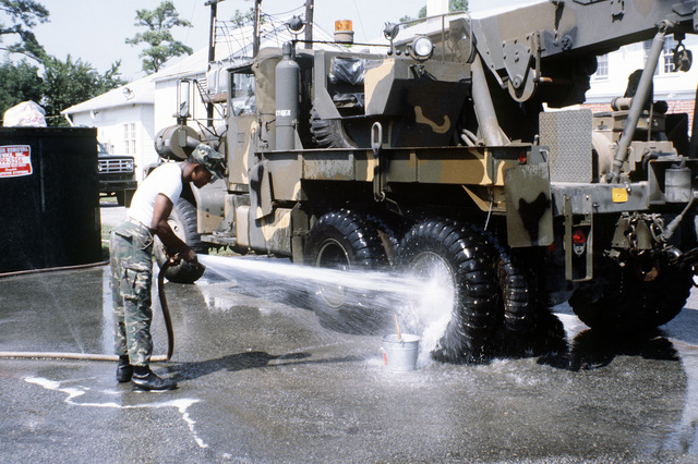 A Marine from the 2nd Maintenance Battalion washes a camouflaged 5-ton wrecker prior to it being loaded aboard a cargo ship in support of a possible rapid deployment of a 12,000-troop amphibious brigade operation