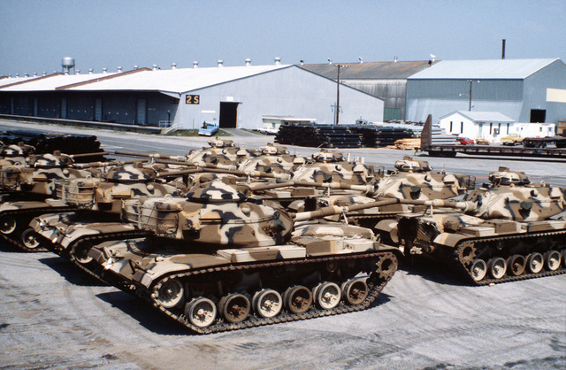A view of Marine M60A1 tanks parked in a staging area prior to being placed aboard a ship in support of a possible rapid deployment of a 12,000-troop amphibious brigade operation. Marines from the 2nd Force Service Support Group are performing the work