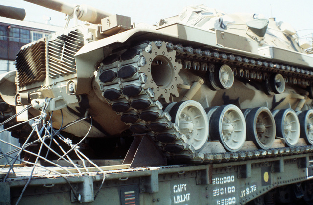Low angle left front view of a Marine M-60A1 tank tied down onto a railroad flatcar. The tanks are to be offloaded and placed aboard ships in support of the possible rapid deployment of a 12,000-troop Marine amphibious brigade operation. Marines of the 2nd Force Service Support Group are performing the work
