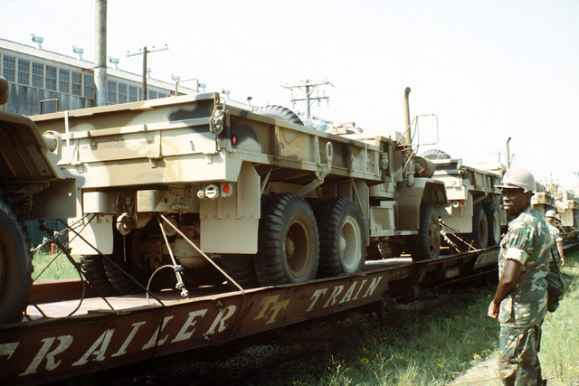 Marine camouflaged M-54 5-ton trucks are prepared for transfer from railroad flatcars to a cargo ship in support of a possible rapid deployment of a 12,000-troop amphibious brigade operation. Marines from the 2nd Force Service Support Group are performing the work
