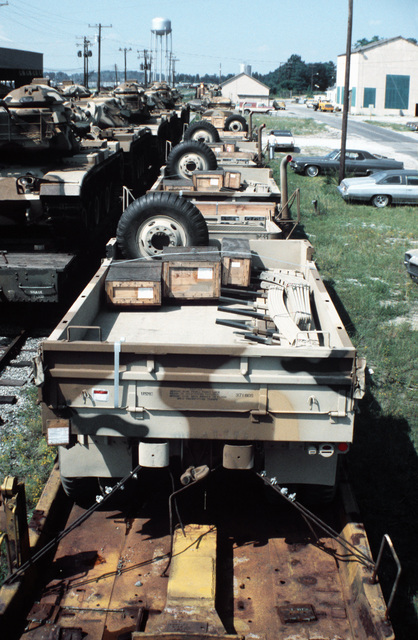 Marine camouflaged M54 5-ton trucks and M60A1 tanks are prepared for transfer from flatcars to a cargo ship in support of a possible rapid deployment of a 12,000-troop brigade operation. Marines from the 2nd Force Service Support Group are performing the work