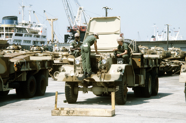 Marine from the 2nd Maintenance Battalion, 2nd Force Service Support Group, perform a maintenance inspection on a Marine camouflaged M-54 5-ton truck in a staging area. The equipment will be placed aboard a cargo ship in support of a possible rapid deployment of a 12,000-troop amphibious brigade operation