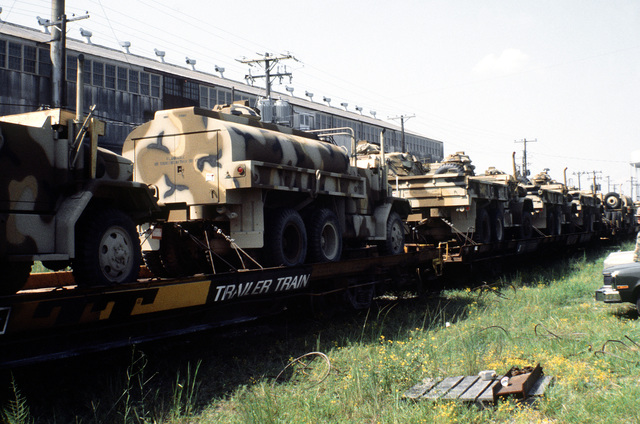 Marine M-54 5-ton trucks and water tank trucks are prepared for transfer from railroad flatcars to a cargo ship in support of a possible rapid deployment of a 12,000-troop amphibious brigade operation