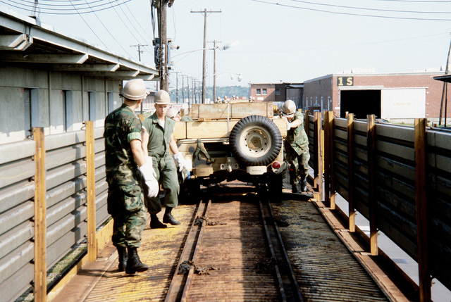 Marines from the 2nd Maintenance Battalion, 2nd Force Service Group, offload M-151A1 jeeps from a double decked railroad flatcar, to be placed aboard ships in support of a possible rapid deployment of a 12,000-troop Marine amphibious brigade operation