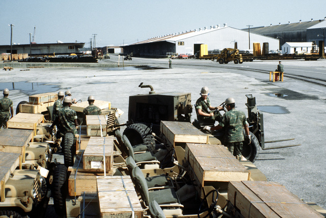 Marines from the 2nd Maintenance Battalion, 2nd Force Service Support Group, unhook an M-151A1 jeep from a forklift at the staging area. The jeep, along with other equipment, will be loaded aboard a cargo ship in support of a possible rapid deployment of a 12,000-troop Marine amphibious brigade operation