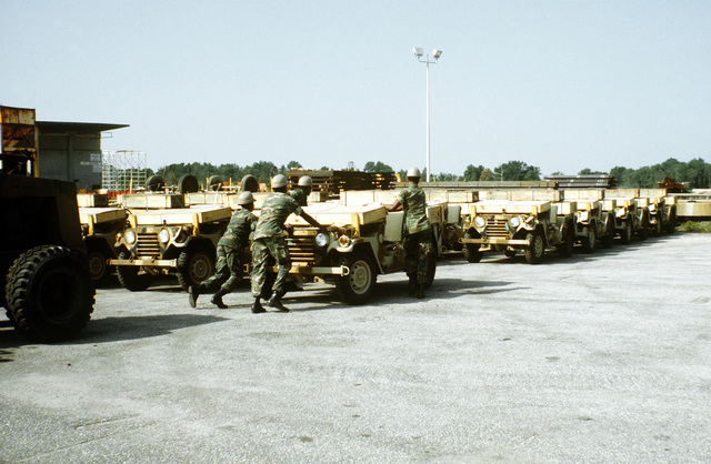 Marines from the 2nd Maintenance Battalion, 2nd Force Service Support Group, push an M-151A1 jeep into position at the staging area. The jeep, along with other equipment, will be loaded aboard a cargo ship in support of a possible rapid deployment of a 12,000-troop Marine amphibious brigade operation