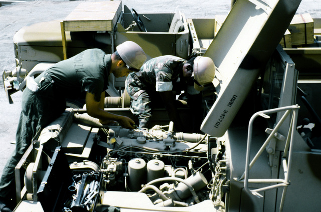 Marines from the 2nd Maintenance Battalion, 2nd Force Service Support Group, perform preventive maintenance on a Marine camouflaged M-54 5-ton truck in a staging area. The equipment will be placed aboard a cargo ship in support of a possible rapid deployment of a 12,000-troop amphibious brigade operation