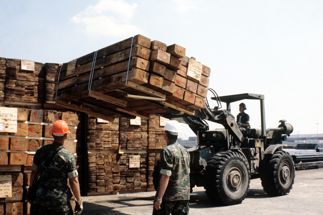 Marines from the Maintenance and Handling Equipment Platoon, 2nd Force Service Group, use a forklift to stack 8x12 inch wooden planks. The planks are used as safety blocks for equipment being loaded aboard railroad flatcars
