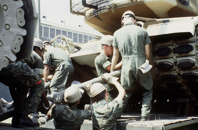 Marines hook up a tow bar to a Marine M-60A1 tank, so that it can be offloaded from a railroad flatcar and placed aboard a ship in support of the possible rapid deployment of a 12,000-troop Marine amphibious brigade operation. Marines of the 2nd Force Service Support Group are performing the work
