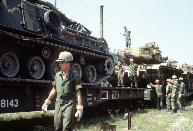 Marines prepare to offload an M-60A1 tank from a railroad flatcar to be placed aboard a ship, in support of the possible rapid deployment of a 12,000-troop Marine amphibious brigade operation. Marines of the 2nd Force Service Support Group are performing the work