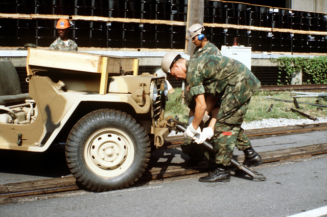 Two Marines from the 2nd Force Service Support Group, place a tow bar on an M-151A1 jeep for towing to a staging area. The equipment will then be placed aboard ships in support of a possible rapid deployment of a 12,000-troop Marine amphibious brigade operation
