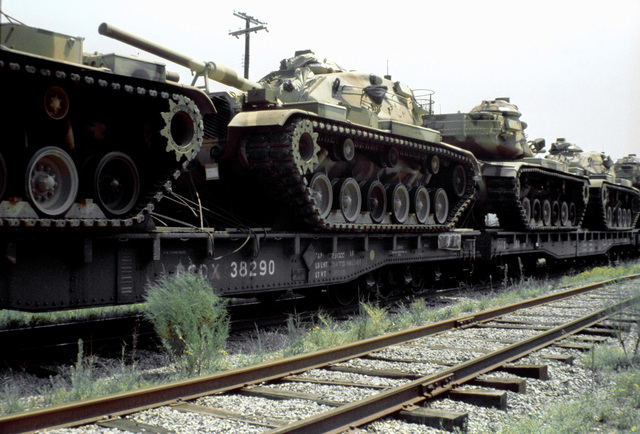 View of Marine M-60A1 tanks on railroad flatcars prior to being offloaded and placed aboard ships, in support of the possible rapid deployment of a 12,000-troop Marine amphibious brigade operation. Marines of the 2nd Force Service Support Group are performing the work