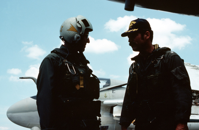 Admiral Thomas B. Hayward, CHIEF of Naval Operations, discusses flight plans with the flight captain prior to taking-off for the attack aircraft carrier USS MIDWAY (CVA 41) for a visit. The A-6 Intruder aircraft that he will fly in is behind them