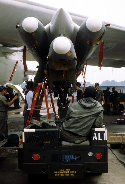 The missile crew from the 416th Bomb Wing, position and mount three Air-Launched Cruise Missiles to the pylon of a B-52G Stratofortress aircraft