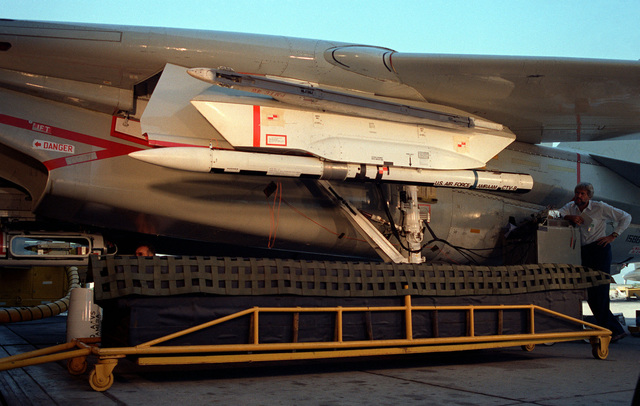 "An Advanced Medium Range Air-to-Air Missile (AMRAAM) before it is dropped into a ""Catcher's Mitt"" during a ground ejection test from the wing of an F-14A Tomcat aircraft at the Pacific Missile Test Center"