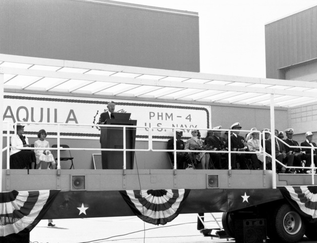 Boeing Marine Systems Vice President R.E. Bateman speaks at the launching of the guided missile patrol combatant (hydrofoil) AQUILA (PHM-4) as other distinguished guests on the speaker's platform listen. Among the guests is RDML James Williams, second from right, commander, Naval Base Seattle. The AQUILA was built by Boeing Marine Systems