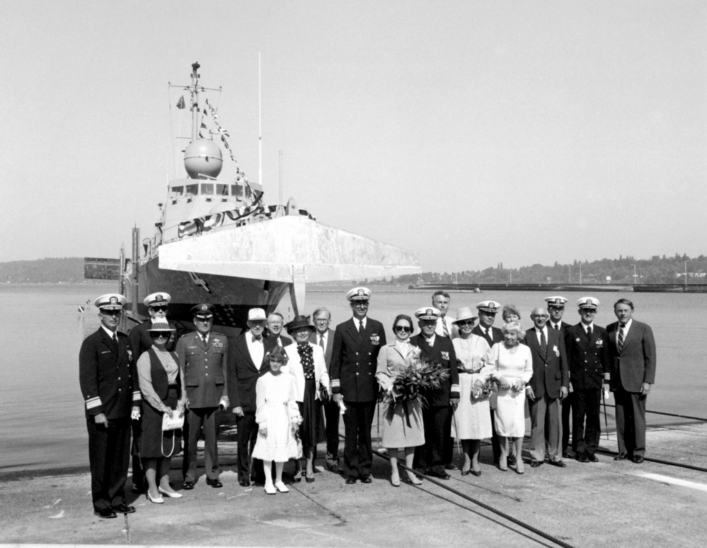 Distinguished guests stand on the pier at the bow of the guided missile patrol combatant (hydrofoil) AQUILA (PHM-4) following launching. Among the guests are RDML and Mrs. John D. Williams, left; RDML and Mrs. James W. Lisanby, center; and RDML and Mrs. John D. Bulkeley. Mrs. Bulkeley, holding flowers, is the ship's sponsor. Her husband is at her left. The AQUILA was built by Boeing Marine Systems