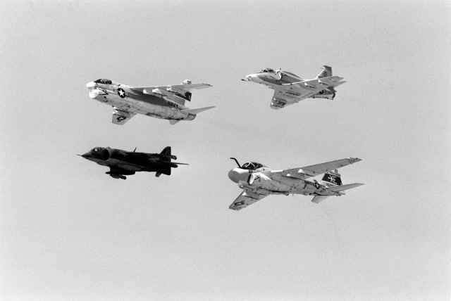 Ground-to-air view of four aircraft flying in formation during Test and Evaluation Squadron Five (VX-5) airshow. The aircraft over Armitage Field, are (from left to right, clockwise) an A-7E Corsair II, an A-4M Skyhawk, and A-6E Intruder and an AV-8C Harrier