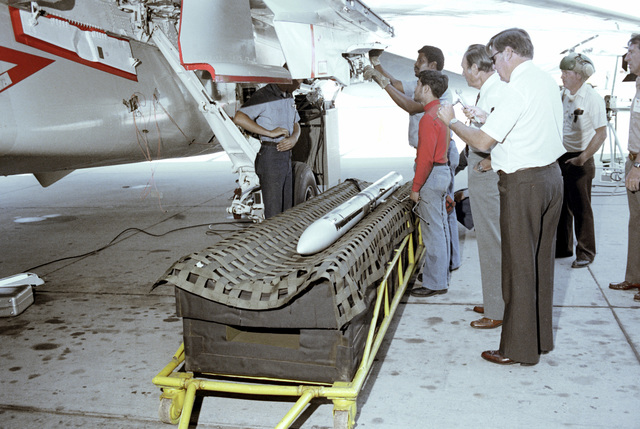 Personnel check on an F-14A Tomcat aircraft after an advanced medium range air-to-air missile (AMRAAM) is ejected during a ground ejection test at the Pacific Missile Test Center