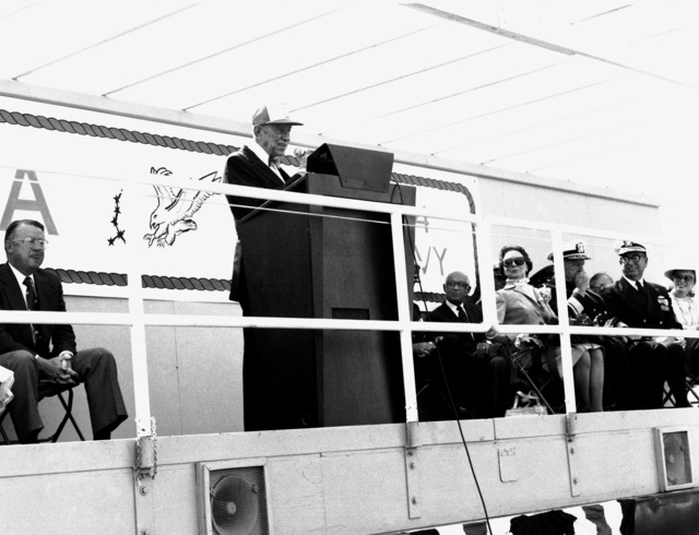 Retired LT J. M. Newberry, USN, speaks at the launching of the guided missile patrol combatant (hydrofoil) AQUILA (PHM-4) as other distinguished guests on the speaker's platform listen. Among the guests to Newberry's left are, front row, from left, RDML and Mrs. John D. Bulkeley, RDML James W. Lisanby and Joan Bulkeley Stade. Mrs. Bulkeley is the ship's sponsor and Mrs. Stade is the matron of honor