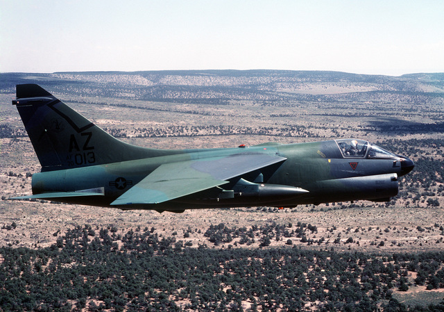 A right side view of an A-7D Corsair II aircraft from Arizona National Guard, in flight. The aircraft, painted in a camouflage color scheme, is being tested against desert and forest backgrounds for visibility