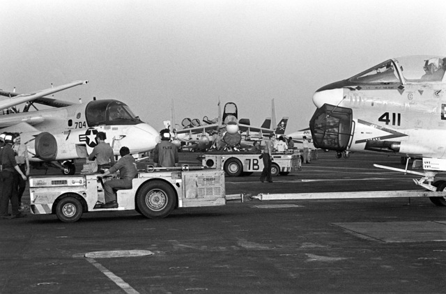 A tow tractor moves an A-7 Corsair II aircraft into parking position aboard the nuclear-powered aircraft carrier USS NIMITZ (CVN-68) during the NATO exercise Display Determination '81