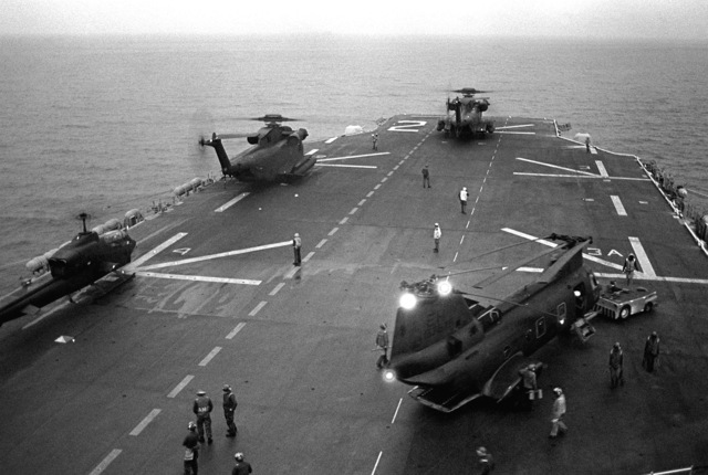 A view of helicopters on the deck of the amphibious assault ship USS SAIPAN (LHA-2).The helicopters are, starting at left: an AH-1 Sea Cobra, two H-53 Sea Stallion and an H-46 Sea Knight. The ship and helicopters are involved in a NATO exercise Display Determination '81