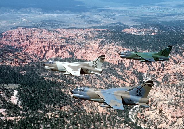 AN air-to-air left side view of three A-7D Corsair II aircraft from Arizona National Guard. The aircraft, each in a different camouflage paint scheme, are being tested against forest and desert backgrounds for visibility