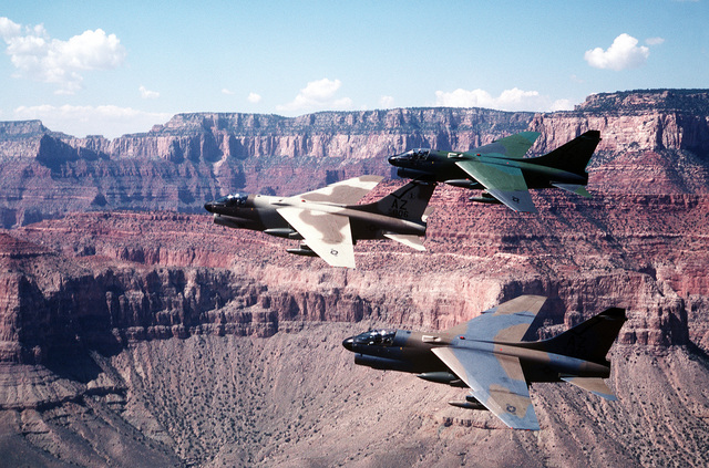 AN air-to-air left side view of three A-7D Corsair II aircraft from the Arizona National Guard. The aircraft, each painted in a different camouflage color scheme, are being tested against forest and desert backgrounds for visibility