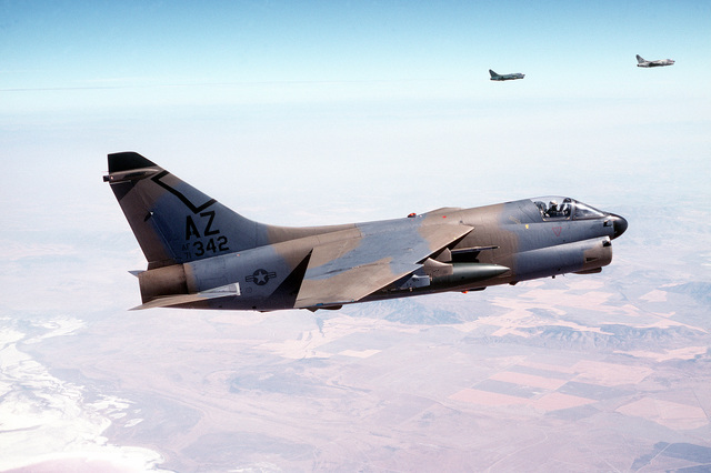AN air-to-air right side of an A-7D Corsair II aircraft from the Arizona National Guard. The aircraft, in a camouflage paint scheme, is being tested over desert and forest background for visibility. In the background are two other A-7s