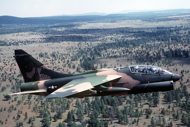 AN air-to-air right side of an A-7K Corsair II aircraft. The aircraft, painted in camouflage, is being tested over desert and forest backgrounds for visibility