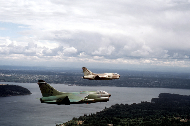 AN air-to-air right side of two A-7D Corsair II aircraft from the Arizona National Guard. The aircraft, in different camouflage paint schemes, are being tested against forest and desert backgrounds for visibility