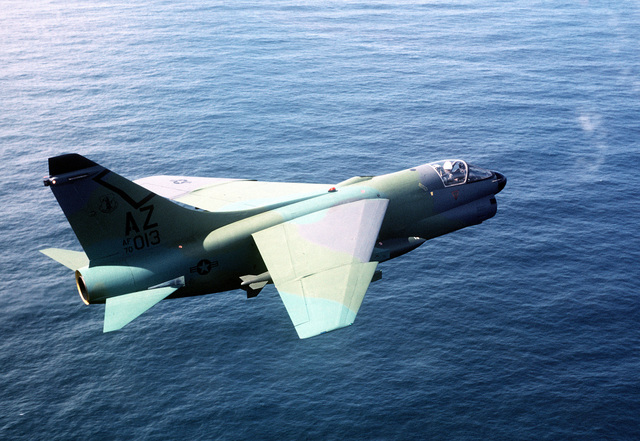 AN air-to-air right side view of an A-7D Corsair II aircraft from the Arizona National Guard. The aircraft in a camouflage paint scheme is being tested against different backgrounds for visibility