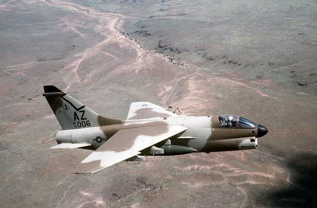AN air-to-air right side view of an A-7D Corsair II aircraft, from the Arizona National Guard. The aircraft, in a camouflage paint scheme, is being tested against a desert background for visibility