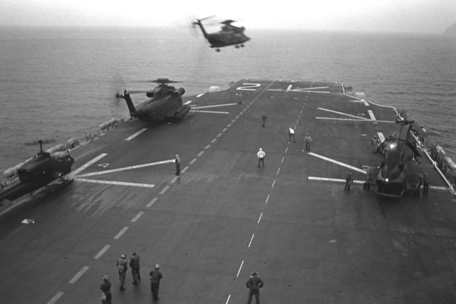 An H-53 Sea Stallion helicopter lifts off the flight deck of the amphibious assault ship USS SAIPAN (LHA-2) during the NATO exercise Display Determination '81. The other helicopters are from left to right: an AH-1 Sea Cobra, an H-53 Sea Stallion and an H-46 Sea Knight