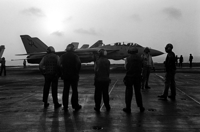 Flight deck crewmen take a break on the deck of the nuclear-powered aircraft carrier USS NIMITZ (CVN-68) during the NATO exercise Display Determination '81.A parked F-14 Tomcat aircraft is in the background