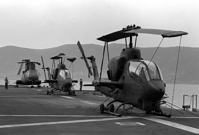 Two AH-1 Sea Cobra and a CH-46 Sea Knight helicopter are secured on the deck of the amphibious ship USS SAIPAN (LHA-2) during NATO exercise Display Determination '81