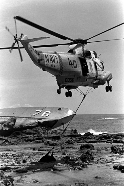 A right rear view of an SH-3A Sea King helicopter from Fleet Composite Squadron 5 (VC-5) as it airlifts bodies from the beached and overturned Filipino frigate RPS DATU KALANTIAW (PS-76) during search and rescue (SAR) operations. The ship was overtaken by Typhoon Clara